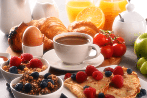 White cup filled with tea surrounded by fresh fruit and oats, boiled egg, cheery tomatoes, fresh oranges and orange Juice, a bagel and croissant