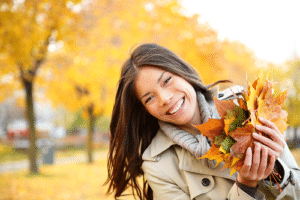 Smiling woman in coat playing with leaves during fall