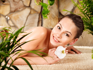 Smiling woman in spa holding flower