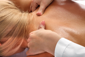 Massage therapist holding woman's neck